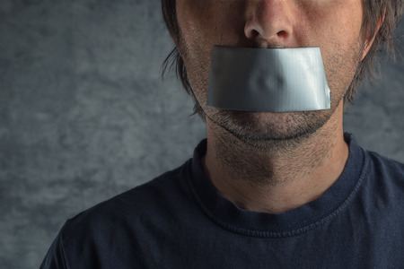 Foto de Censorship, adult caucasian man with duct tape on mouth to prevent him from speaking, freedom of speech and expression concept - Imagen libre de derechos