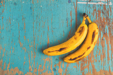 Photo pour Two old ripe bananas on rustic wooden table, top view - image libre de droit