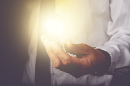 Foto de Business idea and vision, businessman holding light bulb, concept of new ideas, innovation, invention and creativity, retro toned image, selective focus. - Imagen libre de derechos