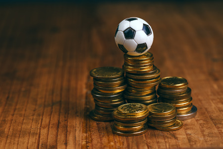 Foto de Soccer bet concept with small football on top of coin stack, making money by predicting sport results. - Imagen libre de derechos