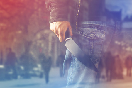 Foto de Evil terrorist man with shiny knife, a killer person with sharp knife about to commit an act of violence or terrorism, homicide, murder scenery, double Exposure - Imagen libre de derechos