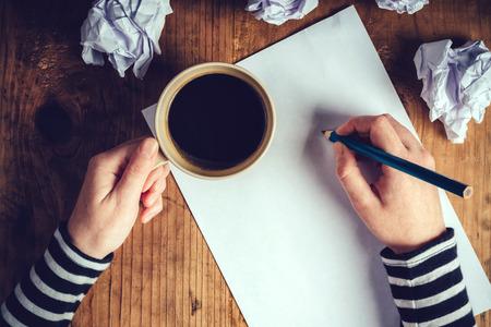 Foto de Female writer drinking cup of coffee, top view of female hands holding cup of coffee above pencils and paper on work desk, retro toned image. - Imagen libre de derechos