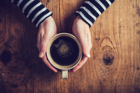 Photo for Lonely woman drinking coffee in the morning, top view of female hands holding cup of hot beverage on wooden desk, retro toned. - Royalty Free Image