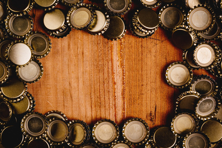 Photo for Beer bottle caps forming frame over oak wood plank as copy space. - Royalty Free Image