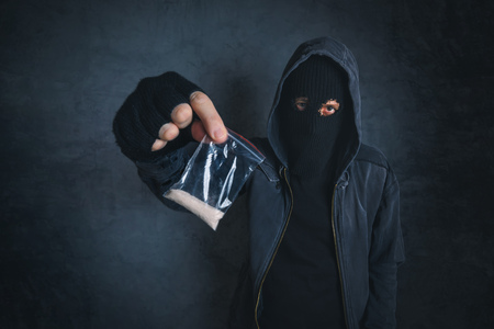 Photo pour Drug dealer offering narcotic substance to addict on the street, unrecognizable hooded criminal selling drugs in dark alley, addicted person point of view image - image libre de droit