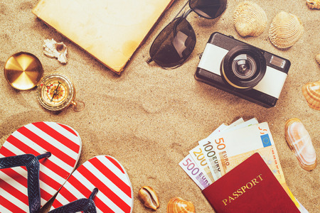 Foto de Summer vacation accessories on tropical sandy ocean beach, holidays abroad - summertime lifestyle objects and European euros in flat lay top view arrangement in warm sand. - Imagen libre de derechos