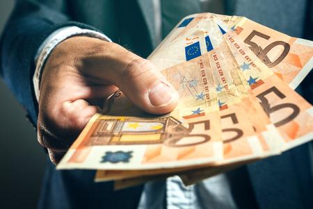 Photo pour Businessman from bank offering money loan in euro banknotes, selective focus. - image libre de droit