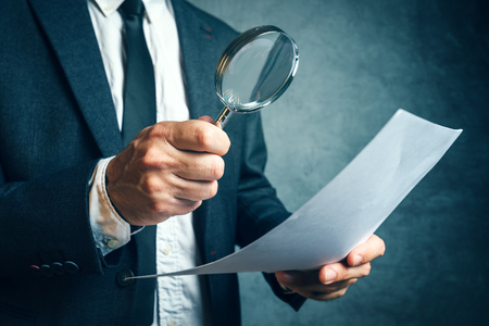 Photo pour Tax inspector investigating financial documents through magnifying glass, forensic accounting or financial forensics, inspecting offshore company financial papers, documents and reports. - image libre de droit