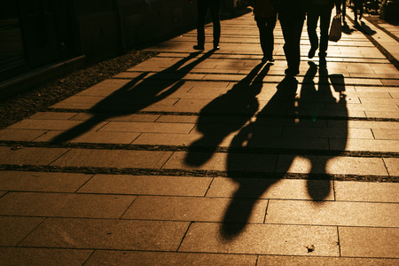 Photo pour Silhouettes of people walking on city street and casting shadows on pavement, general public concept for any community related theme. - image libre de droit