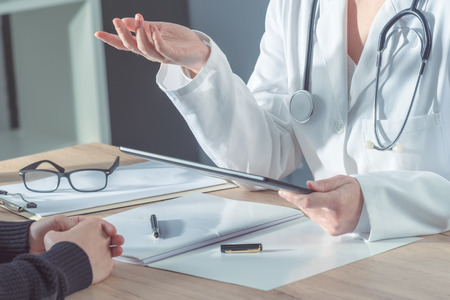 Photo pour Female doctor advising patient in hospital office during regular medical exam, healthcare and prevention concept. - image libre de droit