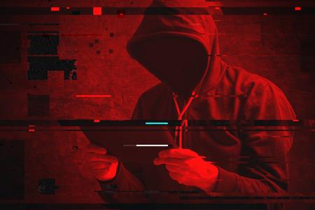 Foto de Cyber attack with unrecognizable hooded hacker using tablet computer, digital glitch effect - Imagen libre de derechos