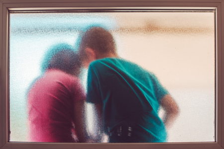 Unrecognizable children, boy and girl behind stained glass window sharing childhood secrets and enjoying warm summer day