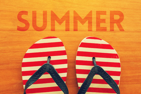 Photo for Summer holidays season is here. Beach sandals flip flops with text Summer on wooden background - Royalty Free Image