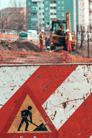Foto de Under construction concept, road works sign with unrecognizable workes in the background - Imagen libre de derechos