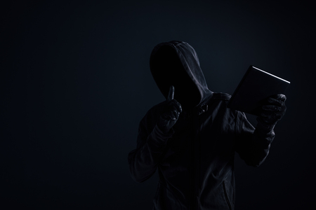 Foto de Hooded computer hacker with obscured face using digital tablet in cybercrime and cybersecurity concept, low key with selective focus - Imagen libre de derechos
