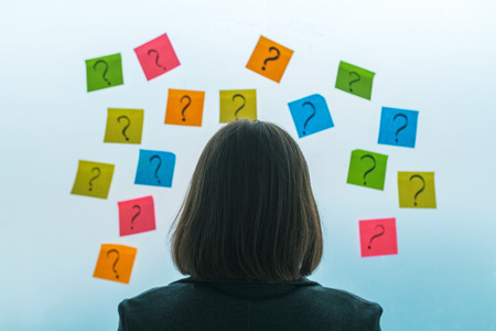 Foto de Businesswoman facing questions and challenges in business situation, rear view of female business person looking at question marks written on colorful sticky note paper - Imagen libre de derechos