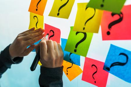 Foto de Businesswoman writing question marks on colorful sticky note paper on office whiteboard, selective focus - Imagen libre de derechos
