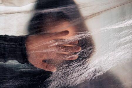 Foto de Drug addiction concept, blurred male person with hoodie behind plastic curtain, selective focus - Imagen libre de derechos