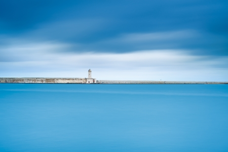 Livorno port lighthouse, breakwater and soft water under cloudy sky  Tuscany, Italy, Europe  Long exposure photography