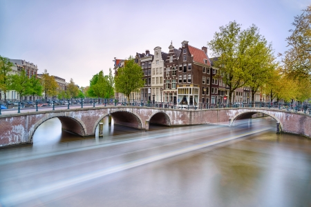 Photo pour Amsterdam  Bridge and water canal  Boat light trail in long exposure on sunset  Holland or Netherlands  Europe  - image libre de droit