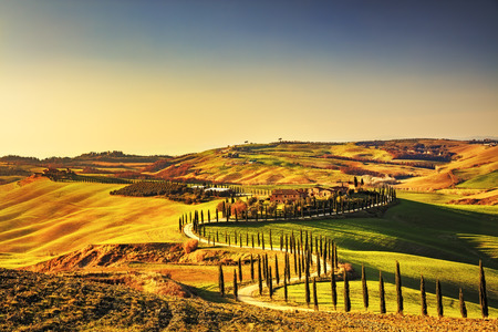 Photo pour Tuscany, Crete Senesi rural sunset landscape. Countryside farm, cypresses trees, green field, sun light and cloud. Italy, Europe. - image libre de droit