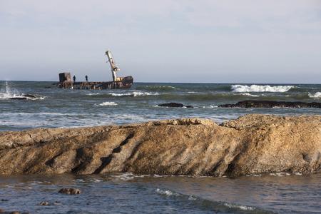 Foto de Salvage work on the wreck of a ship on the Skeleton Coast in Namibia. - Imagen libre de derechos