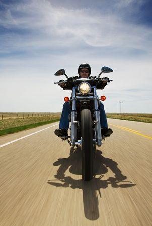 A biker speeding on a rural road