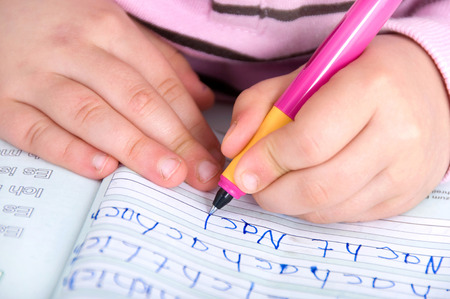 Foto de Childrens hands at the first writing exercises - Imagen libre de derechos
