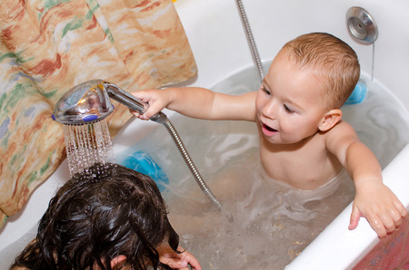 Children playing in the bathtub with the shower head