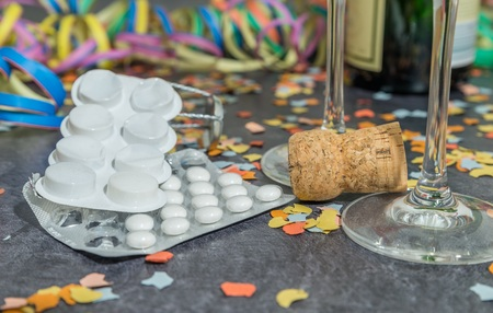 Foto de Pills and alcohol with carnival decoration on a slate - Imagen libre de derechos