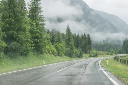 Photo pour Rainy road surface and raindrops on a car windshield - image libre de droit