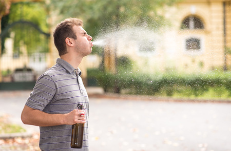 Foto de Young man spit out alcohol in the park - Imagen libre de derechos
