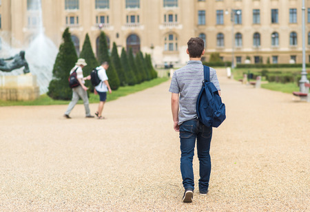 Photo pour Young student walking to the university. Back view photo - image libre de droit