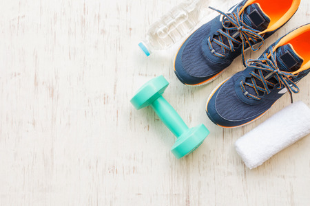 Blue running shoes with fitness accessories on white wooden background