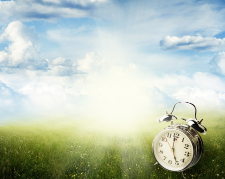 Photo pour Alarm clock in sunlit spring field - image libre de droit
