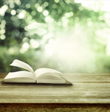 Foto de Open book on table in front of spring background - Imagen libre de derechos