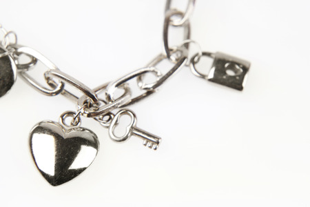 Foto de Closeup of heart and key on charm bracelet - Imagen libre de derechos
