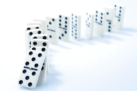Foto de Dominoes on plain background, about to fall - Imagen libre de derechos