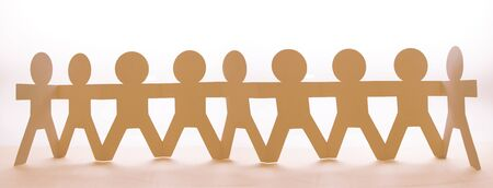 Foto de Team of paper chain people in a row holding hands - Imagen libre de derechos