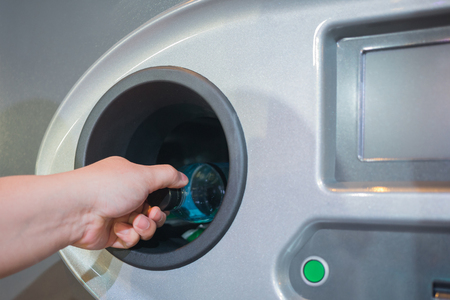 Foto de Reverse Vending Recycling Machine. Recycling machine that dispenses cash. Man hand puts plastic bottle to the machine - Imagen libre de derechos