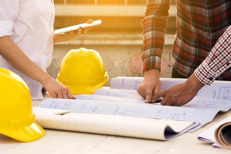 Foto per three construction engineers working outdoors in construction site with blueprint on table - Immagine Royalty Free