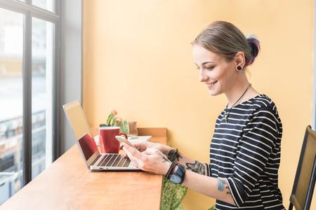 Foto de Russian woman working as freelance use smartphone and laptop in coffee shop - Imagen libre de derechos