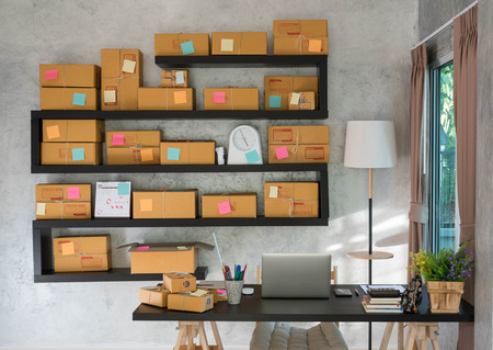 Photo for Work desk with laptop by the window with parcel box prepared for deliver - Royalty Free Image