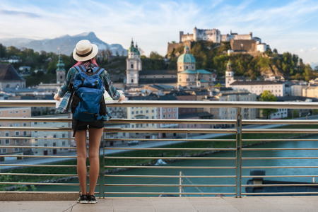 Photo pour Woman westerner travel in backpack with map looking at city view of Castle Salzburg City in Austria - image libre de droit