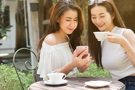 Photo pour Two Beautiful freelance woman use social media on smartphone in coffee shop, modern generation lifestyle - image libre de droit