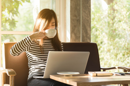 Foto de Beautiful young teenage woman freelance work with laptop have coffee at coffee shop in with sun light, freelance lifestyle conceptual, life of coffee lover - Imagen libre de derechos