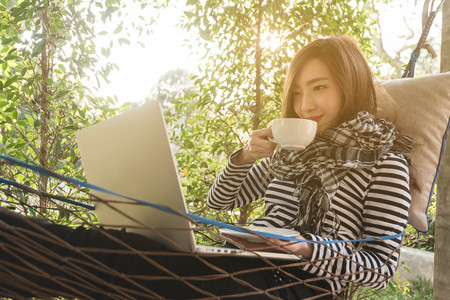 Photo for Young woman having coffee in hammock while use laptop, freelance life style conceptual, work anywhere - Royalty Free Image