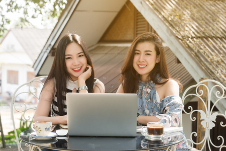 Photo pour Two teenage women meet in coffee shop use laptop together in afternoon, life style of new teenager - image libre de droit