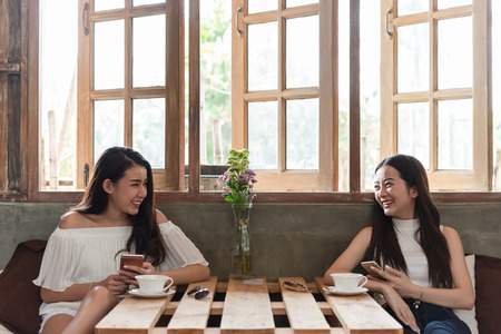 Photo pour Two teenage women meet in coffee shop use smartphone play social media together in afternoon, life style of new teenager - image libre de droit