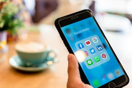 Foto de BANGKOK, THAILAND- 25 June 2019 : Hands of man use Iphone 7 plus with social media application of facebook, youtube, google search, instagram, twitter, linked in, line whatsapp, and pinterest - Imagen libre de derechos